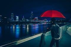 Hombre con el paraguas en orilla del mar de la ciudad moderna imagen de archivo