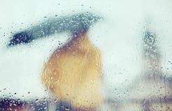 Hombre con el paraguas a través del vidrio mojado Foto de archivo libre de regalías