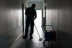Hombre con el pasillo de la oficina de la limpieza de la escoba Foto de archivo libre de regalías