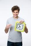 Hombre con el pelo rizado que señala en el reloj Foto de archivo