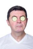 Hombre con el pepino de la rebanada sobre ojos fotos de archivo libres de regalías