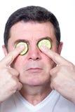 Hombre con el pepino de la rebanada sobre ojos fotografía de archivo