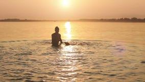 Hombre con el pequeño perrito del beagle que engaña alrededor en ondas de la puesta del sol del océano metrajes