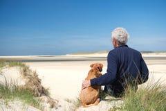 Hombre con el perro en la duna de arena Fotografía de archivo libre de regalías