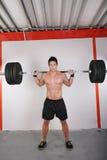 Hombre con el peso de la pesa de gimnasia Fotos de archivo libres de regalías