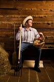 Hombre con el pitchfork, con la cesta de fruta y en sombrero Foto de archivo libre de regalías