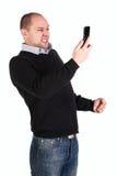 Hombre con el puño y el teléfono móvil apretados Foto de archivo libre de regalías