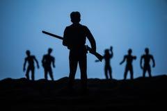 Hombre con el r?pido contra ataque del zombi Apocalipsis del zombi Opini?n asustadiza zombis borrosos en el cementerio y el cielo foto de archivo