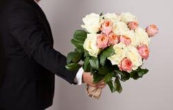 Hombre con el ramo hermoso grande de flores agradables Imagen de archivo