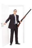 Hombre con el rifle que hace una pausa una puerta Foto de archivo libre de regalías