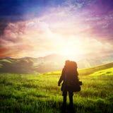 Hombre con el senderismo de la mochila en las montañas Cielo fantástico de la puesta del sol, aventura del verano imagen de archivo libre de regalías