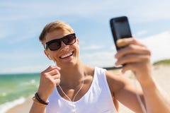 Hombre con el smartphone que toma el selfie en la playa del verano Imagen de archivo
