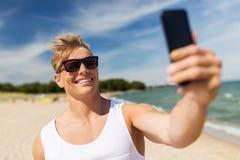 Hombre con el smartphone que toma el selfie en la playa del verano Imagenes de archivo