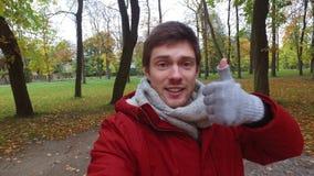 Hombre con el smartphone que toma el vídeo en el parque del otoño