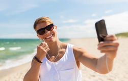 Hombre con el smartphone que toma el selfie en la playa del verano Fotografía de archivo