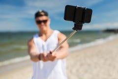 Hombre con el smartphone que toma el selfie en la playa del verano Fotos de archivo