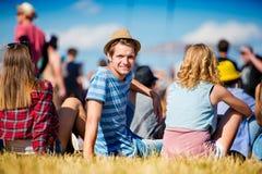 Hombre con el sombrero, adolescentes, festival del verano, sentándose en hierba Fotografía de archivo libre de regalías