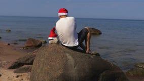 Hombre con el sombrero de Santa Claus que se relaja cerca del mar almacen de video