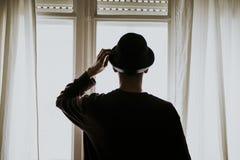 Hombre con el sombrero que mira hacia fuera la ventana Fotografía de archivo libre de regalías