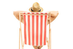 Hombre con el sombrero que se sienta en una silla de playa fotos de archivo