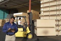 Hombre con el tablero en Front Of Forklift Stacking Boxes imagen de archivo libre de regalías