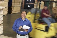 Hombre con el tablero en Front Of Forklift In Warehouse fotos de archivo libres de regalías