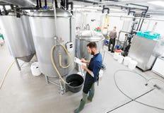 Hombre con el tablero en la cervecería del arte o la planta de la cerveza fotografía de archivo