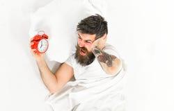 Hombre con el tatuaje y barba que tiene problema que despierta imagen de archivo