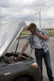 Hombre con el teléfono al lado de su coche quebrado imágenes de archivo libres de regalías