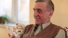 Hombre con el teléfono celular El hombre mayor comunica vía smartphone metrajes