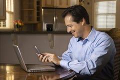 Hombre con el teléfono celular y la computadora portátil Fotografía de archivo libre de regalías