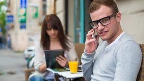 Hombre con el teléfono celular y la mujer con el iPad que se sienta en un café. Fotografía de archivo libre de regalías