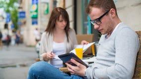 Hombre con el teléfono celular y la mujer con las notas que se sientan en un café. Imagenes de archivo