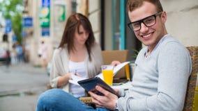Hombre con el teléfono celular y la mujer con las notas que se sientan en un café. Fotos de archivo