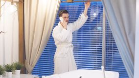 Hombre con el teléfono a disposición que espera el comienzo de los procedimientos, haciendo una pausa la ventana panorámica con v metrajes
