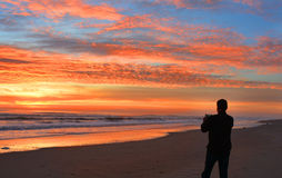 Hombre con el teléfono en la playa en la salida del sol Fotos de archivo