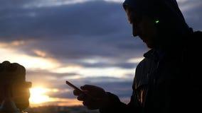 Hombre con el teléfono en un fondo del cielo hermoso y de la puesta del sol Cámara lenta 1920x1080 HD lleno almacen de video