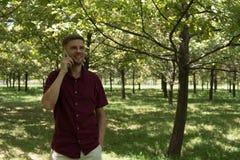 Hombre con el teléfono móvil en parque del verano Hombre hermoso joven con el SM Imagen de archivo libre de regalías