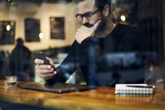 Hombre con el teléfono móvil para crear la publicación que charla con los colegas y el redactor vía smartphone y wifi fotos de archivo libres de regalías