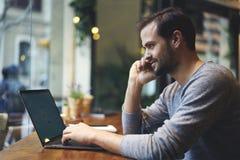 Hombre con el teléfono móvil que arregla la reunión para discutir la colaboración mientras que se sienta en café Imágenes de archivo libres de regalías