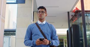 Hombre con el teléfono móvil que camina en el vestíbulo 4k almacen de metraje de vídeo
