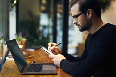 Hombre con el teléfono móvil que trabaja en cafetería usando la conexión a internet del ordenador portátil y de la radio Fotografía de archivo