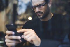 Hombre con el teléfono móvil usando la conexión a internet inalámbrica a confirmar o actualizar enviado Imágenes de archivo libres de regalías