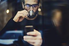 Hombre con el teléfono móvil usando la conexión a internet inalámbrica a confirmar o actualizar enviado Fotografía de archivo