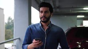 Hombre con el teléfono móvil y los auriculares blancos en el aparcamiento almacen de metraje de vídeo