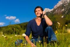 Hombre con el teléfono que se sienta en las montañas Foto de archivo libre de regalías