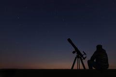 Hombre con el telescopio de la astronomía que mira las estrellas foto de archivo