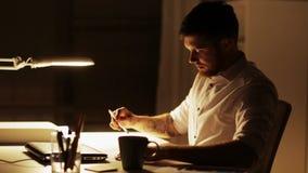 Hombre con el trabajo del acabamiento del ordenador portátil en la oficina de la noche metrajes