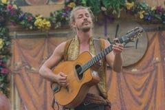 Hombre con el traje medieval que canta y que toca la guitarra Foto de archivo libre de regalías