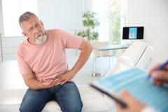 Hombre con el urólogo que visita del problema de salud imagen de archivo